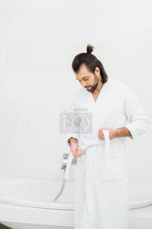Photo pour Bel homme délier peignoir dans la salle de bain blanche - image libre de droit