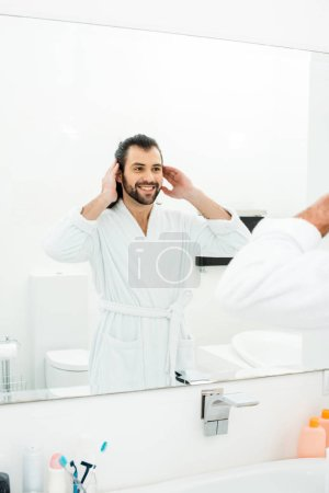 Handsome man looking in mirror and smiling in white bathroom