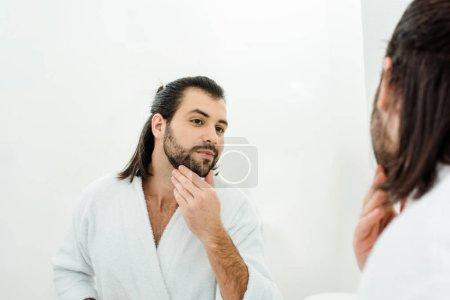 Bel homme toucher barbe et regardant dans le miroir