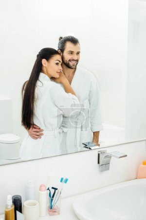 tender couple  in white bathrobes hugging in bathroom at morning