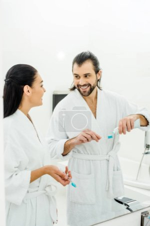 happy couple in white bathrobes brushing teeth together