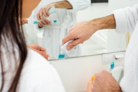 cropped view of man adding toothpaste on woman toothbrush