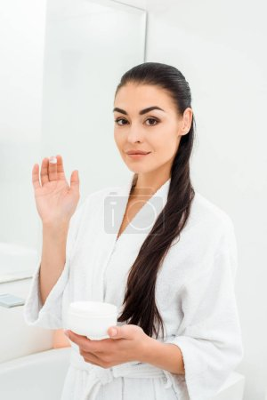 woman with perfect skin showing face cream on fingers