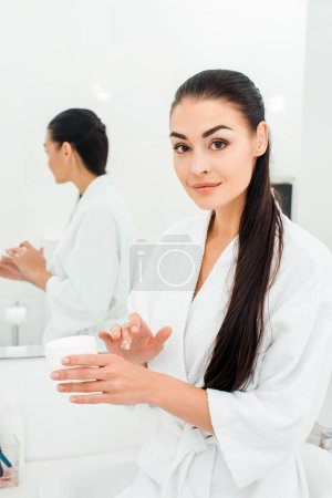 beautiful woman in white bathrobe applying body cream