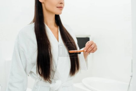 cropped view of woman combing long hair with hairbrush in bathroom