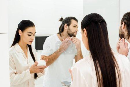Photo pour Belle femme tenant le corps crème tout en bel homme regardant miroir - image libre de droit