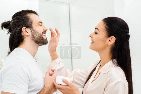 Photo pour Souriant application crème pour le visage femme sur le nez de l'homme dans la salle de bain - image libre de droit