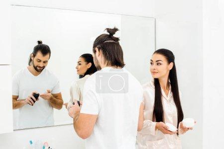 beautiful wife holding body cream while handsome husband applying shaving foam