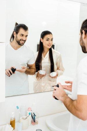 Photo pour Séduisante femme tenant le corps crème tout en beau mari appliquer la mousse à raser - image libre de droit