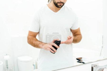 Man holding shaving foam in front of mirror in bathroom