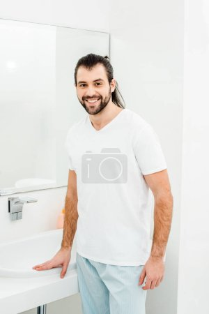 Young man in white T-shirt smiling in bathroom