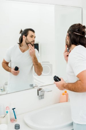 Handsome man holding shaving foam and looking in mirror in bathroom