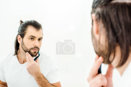 Man looking in mirror and shaving isolated on white