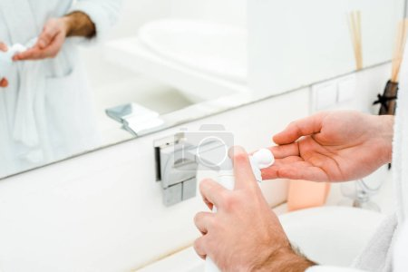 Male hands holding shaving foam in front of mirror in bathroom