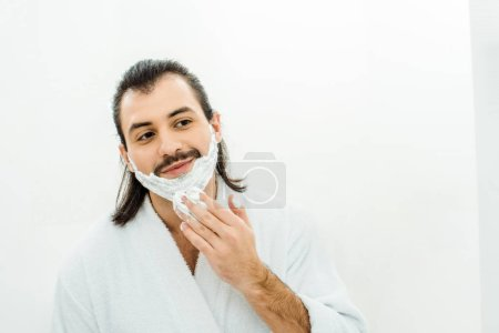 Adult man applying shaving foam in bathroom