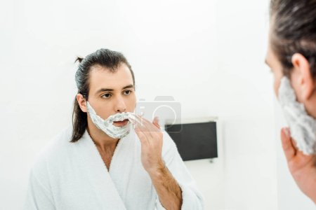 Young man applying shaving foam in front of mirror
