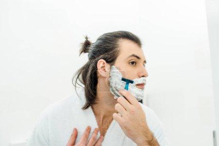 Handsome man in bathrobe shaving in bathroom