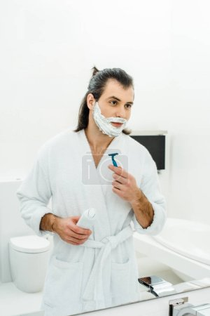 Man in white bathrobe shaving in front of mirror
