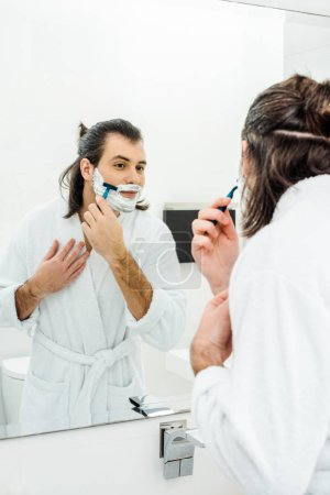 Man smiling and shaving in front of mirror