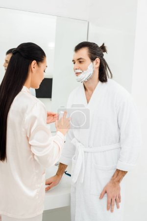 Woman applying shaving foam on husband face