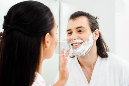 Woman applying shaving foam on smiling husband face