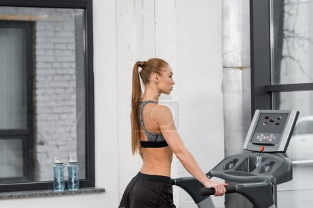 side view of attractive athletic sportswoman training on treadmill in gym