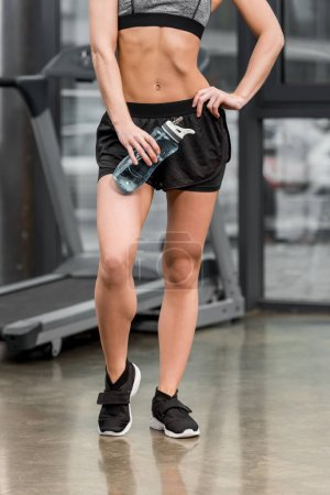 cropped image of athletic sportswoman standing with sport bottle of water in gym