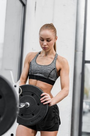 attractive athletic sportswoman putting weights on barbell in gym