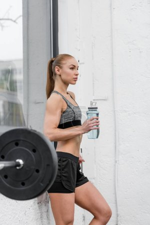 side view of attractive athletic sportswoman resting and standing with sport bottle of water in gym