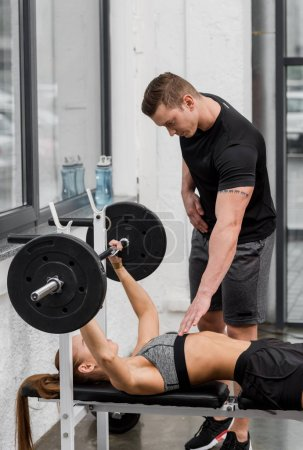 trainer looking at sportswoman lying on bench and lifting barbell in gym