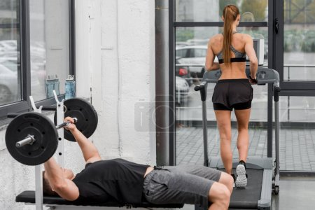sportsman lying on bench and lifting barbell in gym, sportswoman running on treadmill