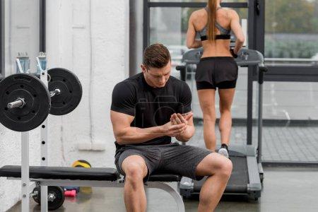 sportsman touching hand on bench, sportswoman running on treadmill in gym