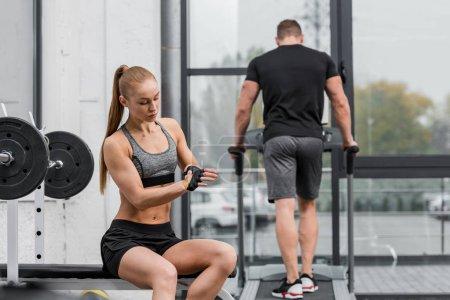 sportsman training on treadmill, sportswoman wearing gloves for training in gym