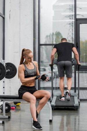 sportsman exercising on treadmill, muscular sportswoman wearing gloves for training in gym