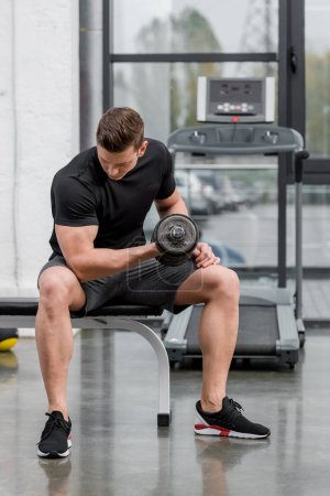 handsome muscular bodybuilder training with dumbbell in gym