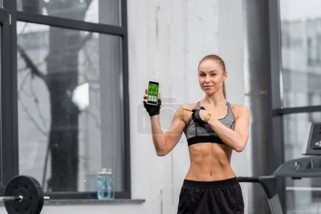 attractive athletic sportswoman pointing on smartphone with medical appliance in gym