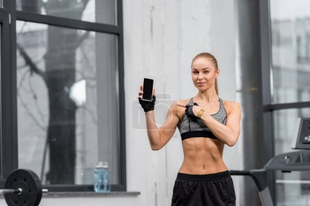 attractive athletic sportswoman pointing on smartphone with blank screen in gym