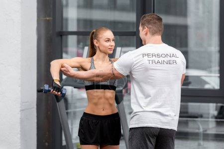 personal trainer helping sportswoman exercising with dumbbells in gym
