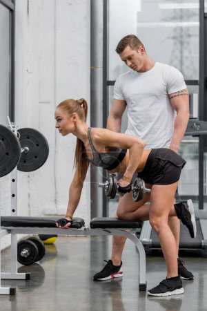 Photo for Personal trainer looking at sportswoman exercising with dumbbells in gym - Royalty Free Image