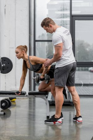personal trainer fixing hand of sportswoman exercising with dumbbells in gym