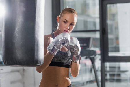 beautiful athletic boxer training with punching bag in gym