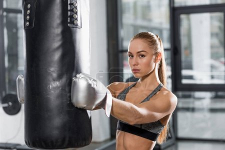 attractive athletic boxer holding punching bag in gym and looking at camera