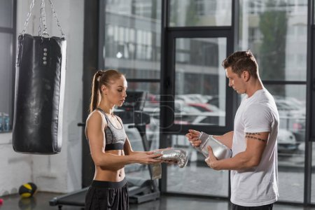 side view of trainer helping wearing silver boxing gloves to attractive boxer in gym