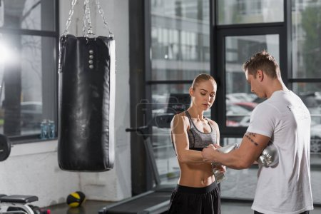 trainer helping wearing silver boxing gloves to attractive boxer in gym