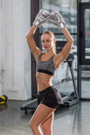 attractive muscular bodybuilder posing with silver boxing gloves and raised hands in gym, looking at camera