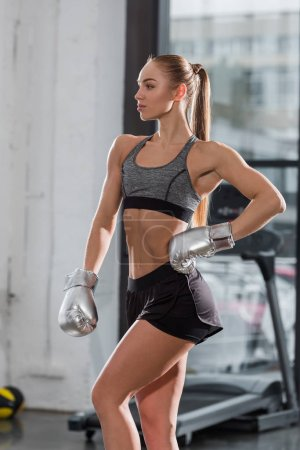 attractive muscular bodybuilder posing with silver boxing gloves in gym