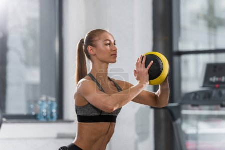 beautiful athletic sportswoman exercising with fitness ball in gym