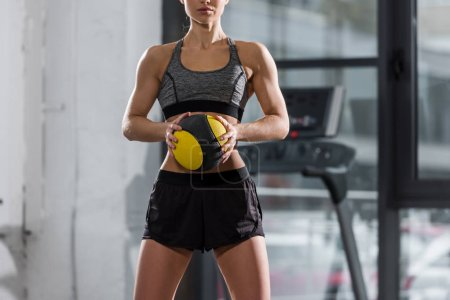 cropped image of muscular sportswoman standing with fitness ball in gym