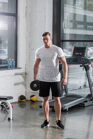 handsome muscular bodybuilder standing with dumbbell in gym and looking at camera