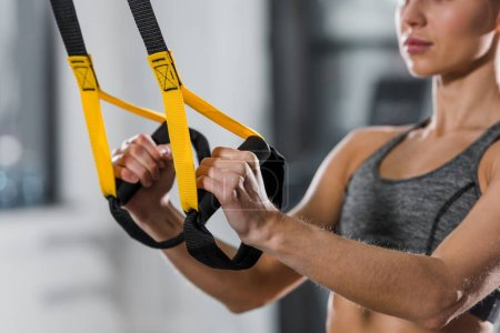 Photo for Cropped image of athletic sportswoman working out with suspension straps in gym - Royalty Free Image